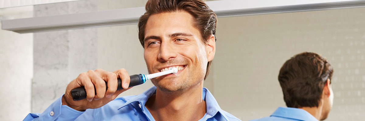 Man brushing his teeth electrically in front of mirror