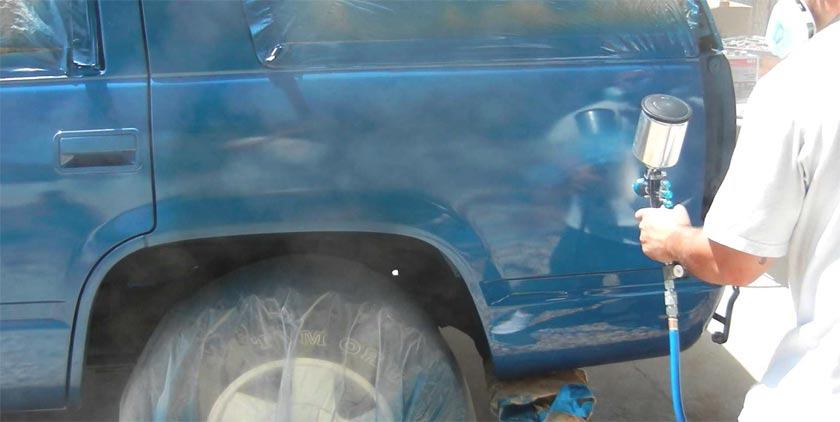 painting a car with the use of an air compressor and paint sprayer