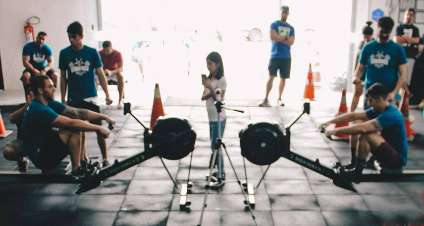 two guys doing rowing exercise in the gym