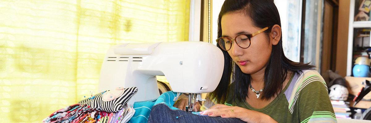 Woman sewing behind sewing machine